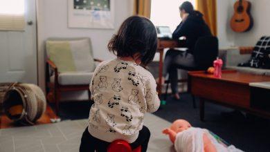 mujer trabajando en su casa mientras su hija juega